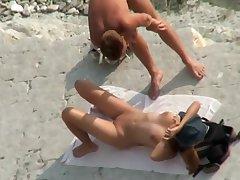 A hotter couple relaxes aloft a nudist beach